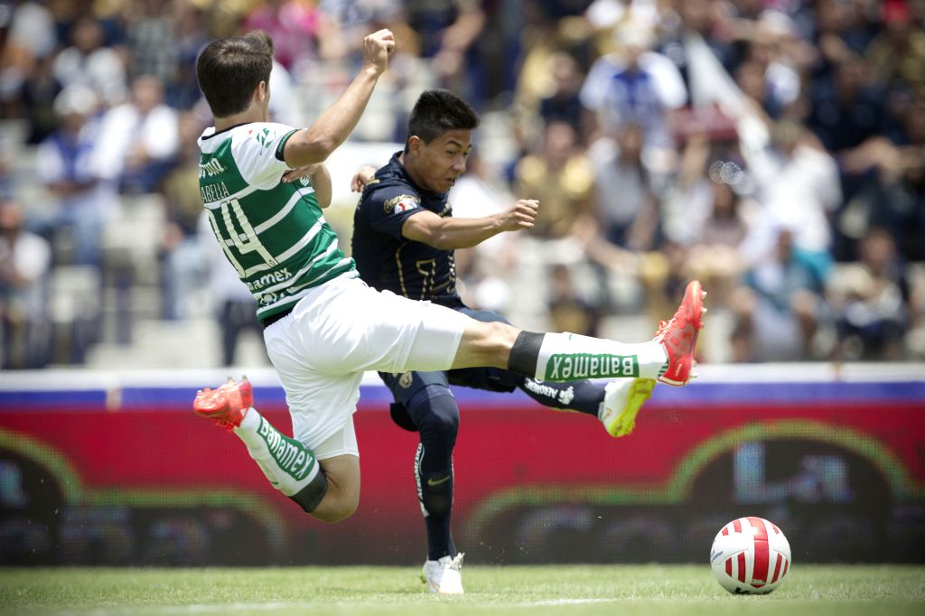 UNAM's Pumas Omar Islas (R) vies for the ball with Santos's Jose Abella during the match of Closing Tournament of the MX League, held in the Olympic University ...