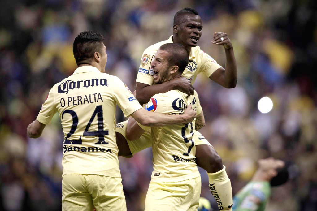 America's Dario Benedetto (C-Below) celebrates after scoring with his teammates Oribe Peralta (L) and Darwin Quintero (R) during the second-leg semifinal match ...