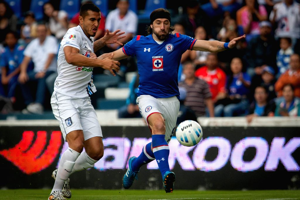 Cruz Azul's Mariano Pavone (R) vies for the ball with Mario Osuna of Queretaro during their match of the MX League Opening Tournament held at Azul Stadium in ...
