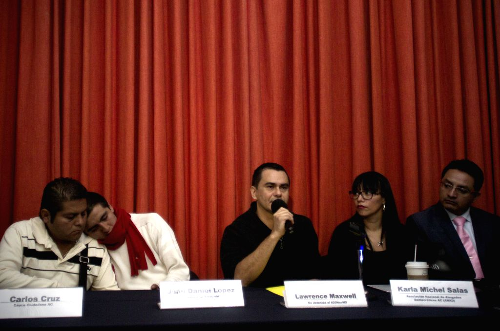 Mexico City: Chilean Lawrence Maxwell (C), and Mexican Juan Daniel Lopez (2nd L), two of the 11 arrested for violent events of Nov. 20, participate in a press conference to give testify for their ...