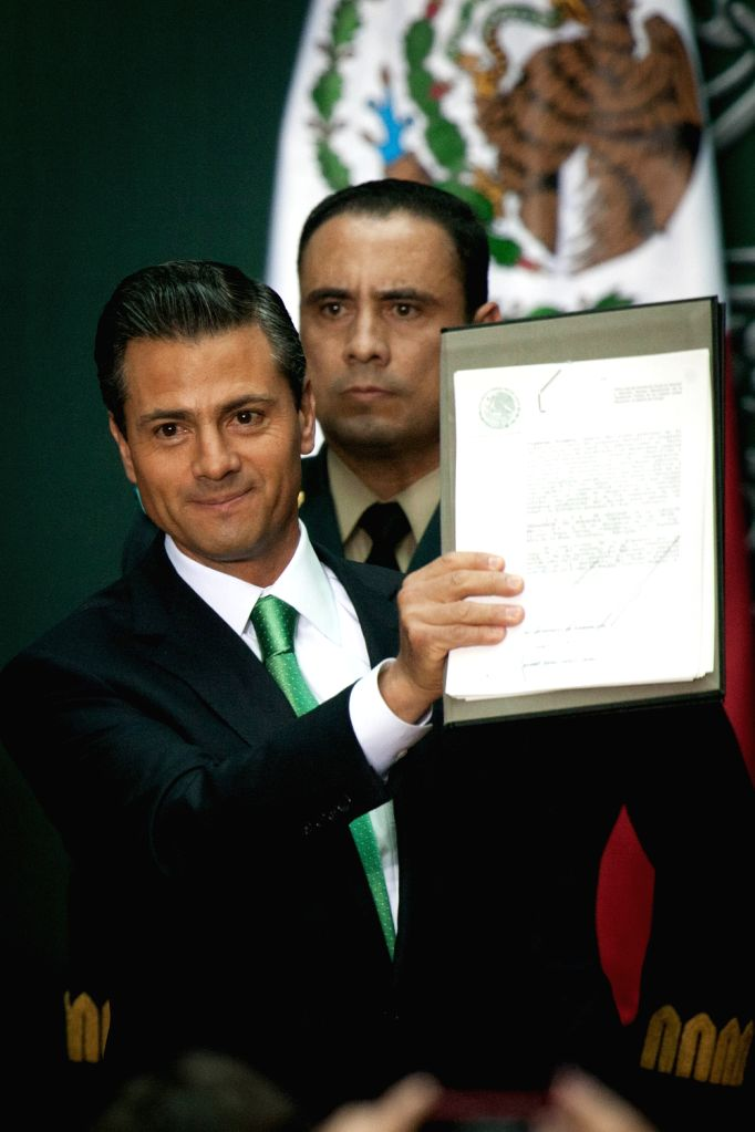 Mexican President Enrique Pena Nieto (Front) shows the documents he signed during the promulgation of the constitutional level energy reform at the ...