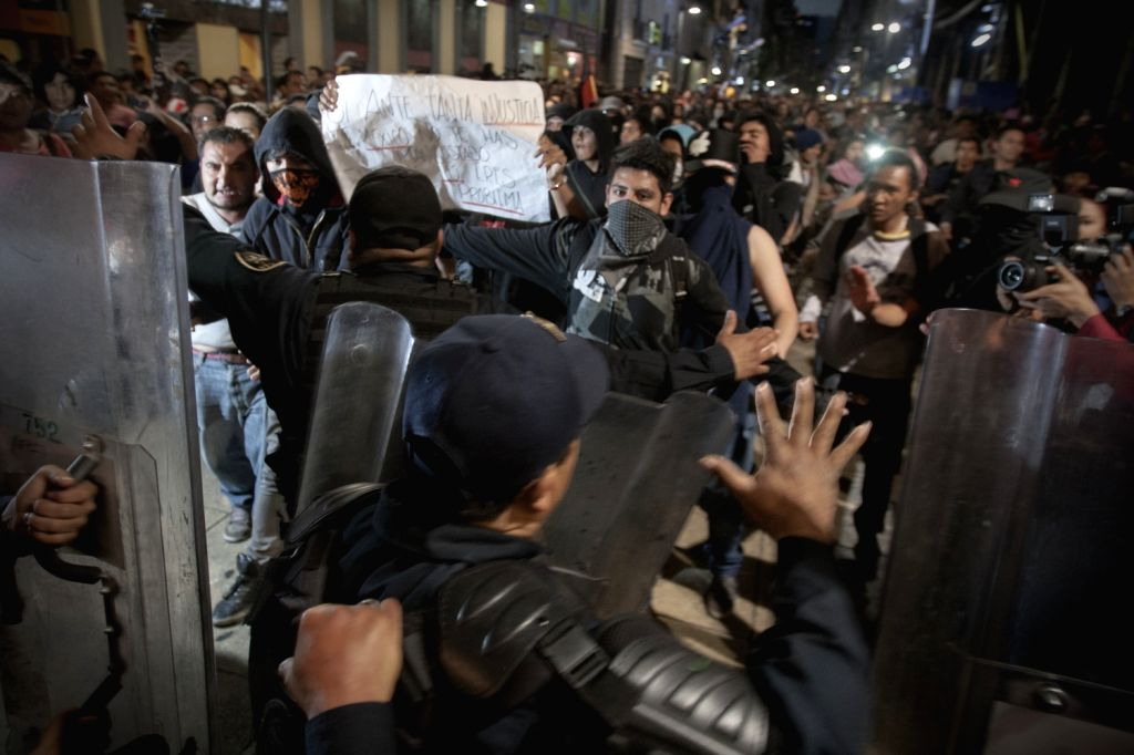 Demonstrators clash with police during a protest against the energy reform in Mexico City, capital of Mexico, on Dec. 20, 2013.