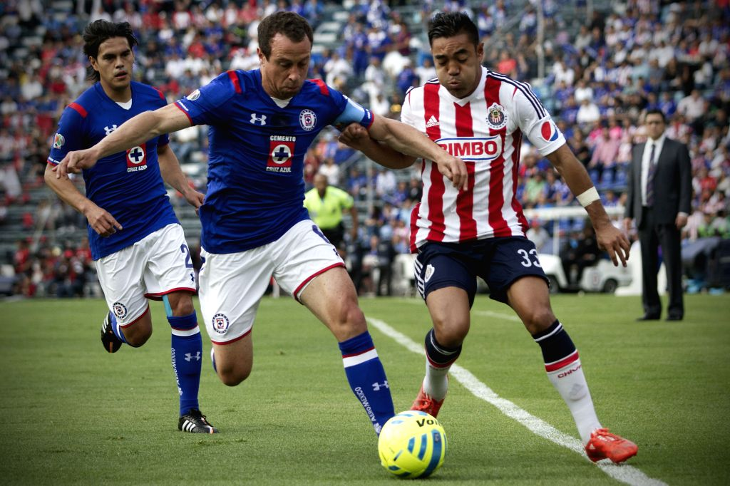 Cruz Azul's Gerardo Torrado (C) vies for the ball with Marco Fabian (R) of Chivas during the match of the 2015 Closing Tournament of MX League in the Azul ...