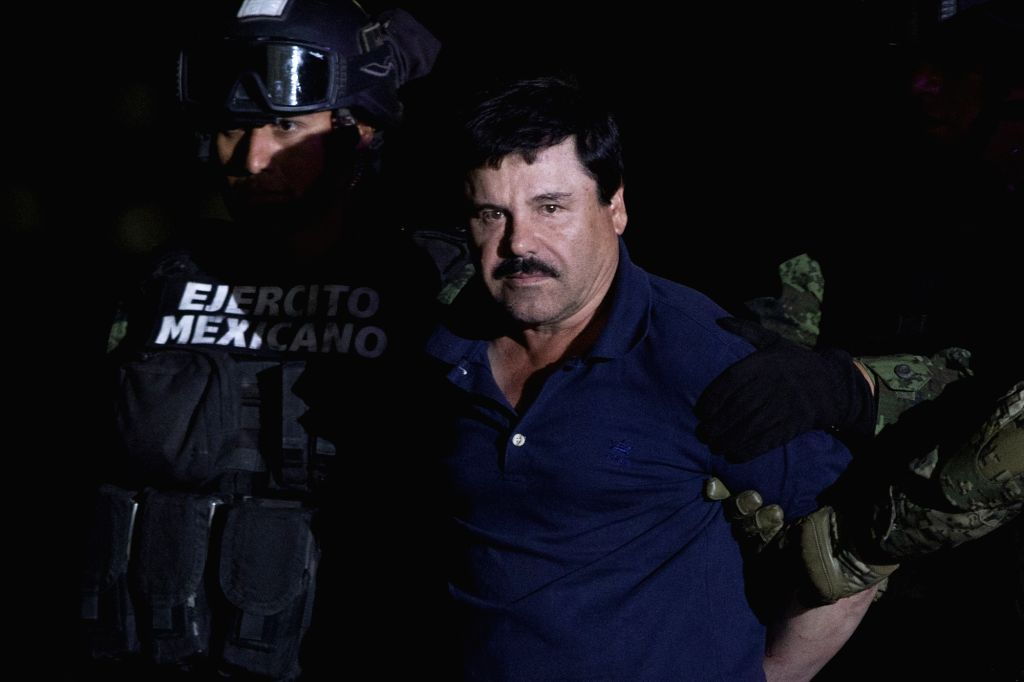 """MEXICO CITY, Jan. 9, 2016 (Xinhua) -- Soldiers escort Joaquin Guzman Loera, alias """"El Chapo"""", upon his arrival to the hangar of the Attorney General's Office, in Mexico City, capital of Mexico, on Jan. 8, 2016. After an early morning raid in northwes"""