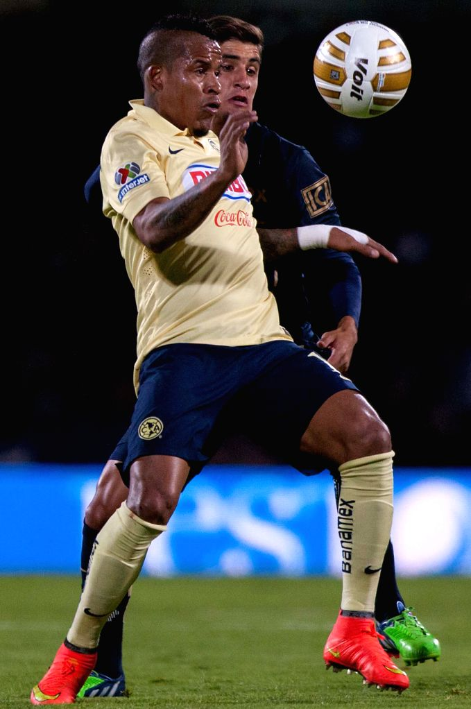 Mexico City: Jose Van Rankin (Back) of UNAM Pumas vies for the ball with Michael Arroyo of America, during the quarterfinals match of Opening Tournament of the MX League at the Olympic Stadium, in ...