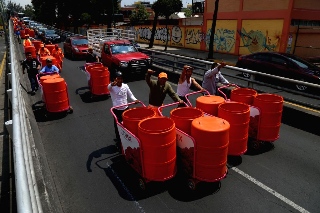MEXICO CITY, March 16, 2017 - Sanitation workers walk in street after they received new trash carts in Mexico City, capital of Mexico, on March 15, 2017. According to local press, in order to improve ...