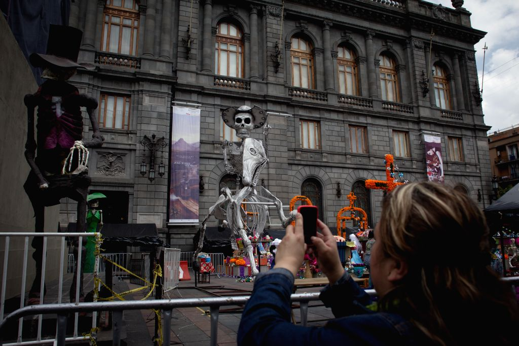 A woman takes photos of the props for the filming of the new James Bond movie Spectre in the downtown of Mexico City, capital of Mexico, on March 18, 2015. ...