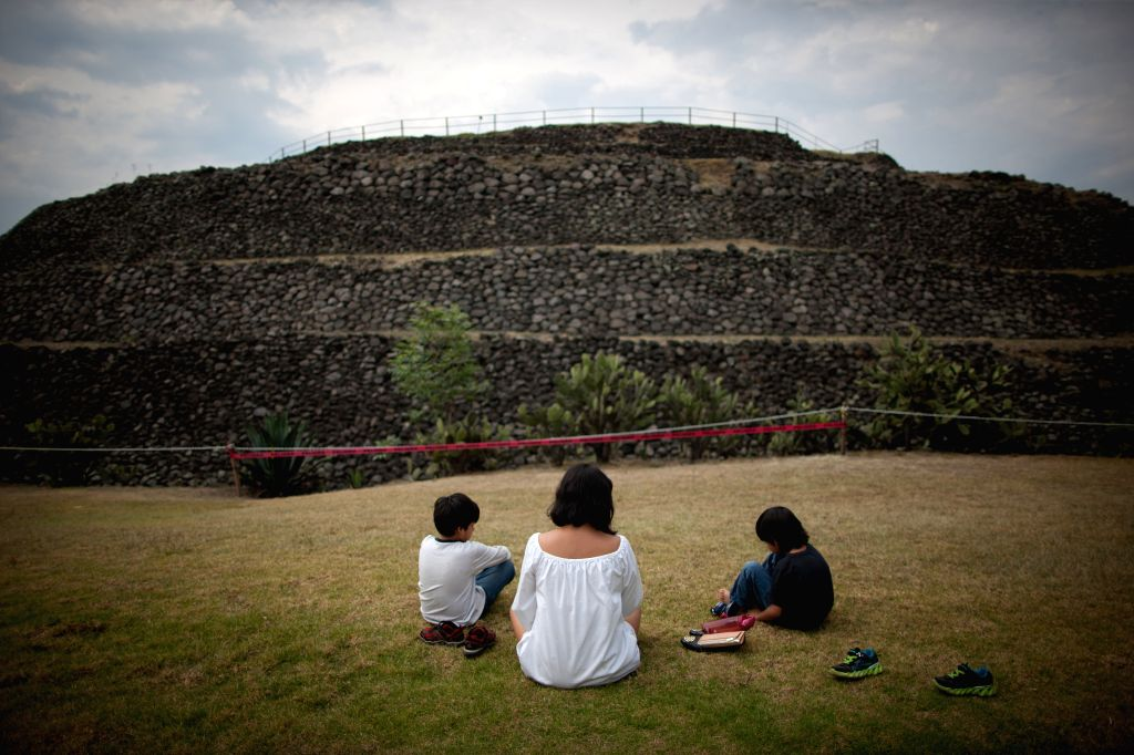 A family waits for the arrival of the spring equinox, in the archaelogical zone of Cuicuilco, in Mexico City, capital of Mexico on March 20, 2015. ...