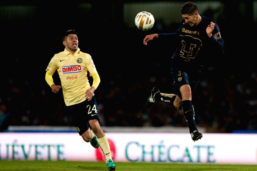 Mexico City: Marco Antonio Palacios (R) of UNAM Pumas vies for the ball with Oribe Peralta of America during the quarterfinals match of Opening Tournament of the MX League at the Olympic Stadium, in .