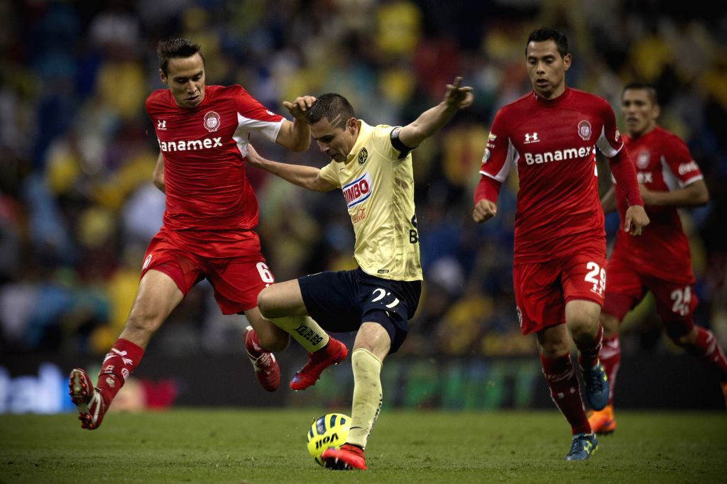 America's Paul Aguilar (C) vies the ball with Toluca's Carlos Rodriguez (L) and Raul Nava during the match corresponding to the Day 16 of the 2015 Closing ...