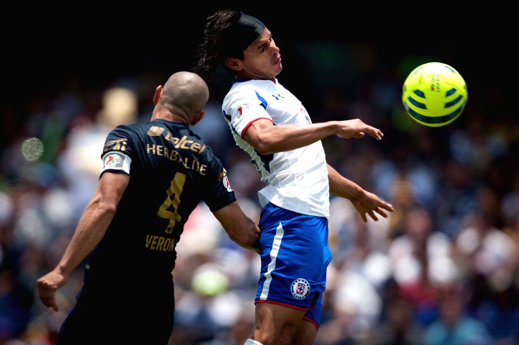 UNAM's Pumas Dario Veron (L) vies with Cruz Azul's Gerardo Flores during the match of Closing Tournament of MX League in the University Olympic Stadium in Mexico ...