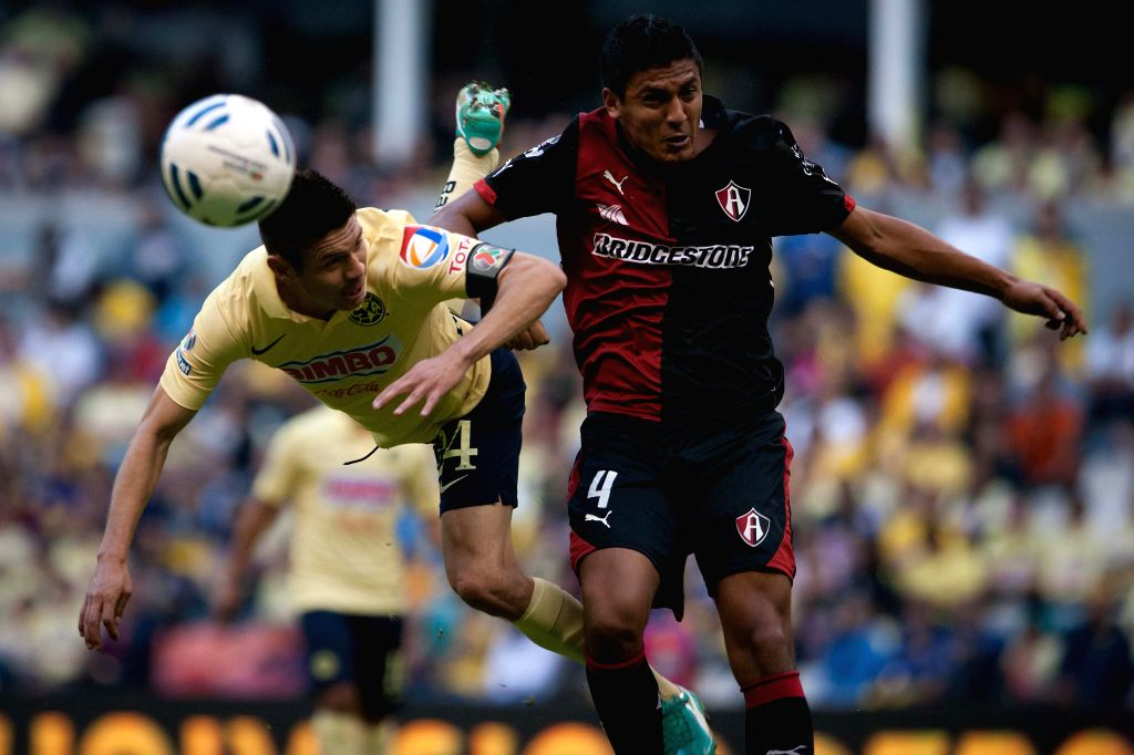 Mexico City Mexico : America's Oribe Peralta (L) vies for the ball with Luis Venegas of Atlas during the match of the Day 17 of the 2014 Opening Tournament of MX League in Azteca Stadium in Mexico .