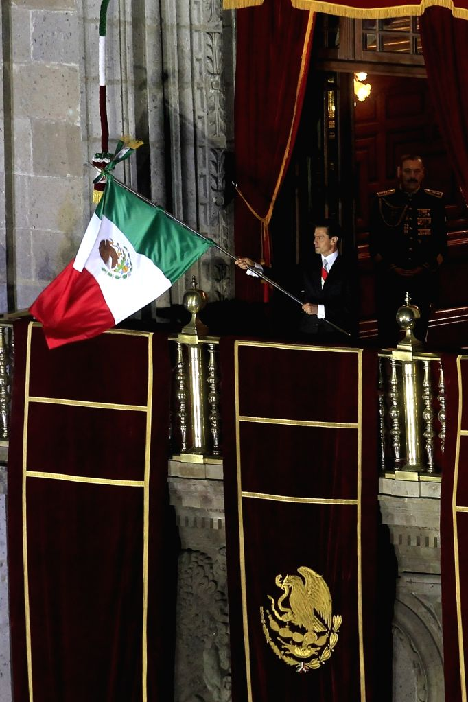 MEXICO CITY, Sept. 16, 2016 - Mexican President Enrique Pena Nieto waves the national flag during the celebrations of the Independence Day from the balcony of the National Palace, in Mexico City, ...