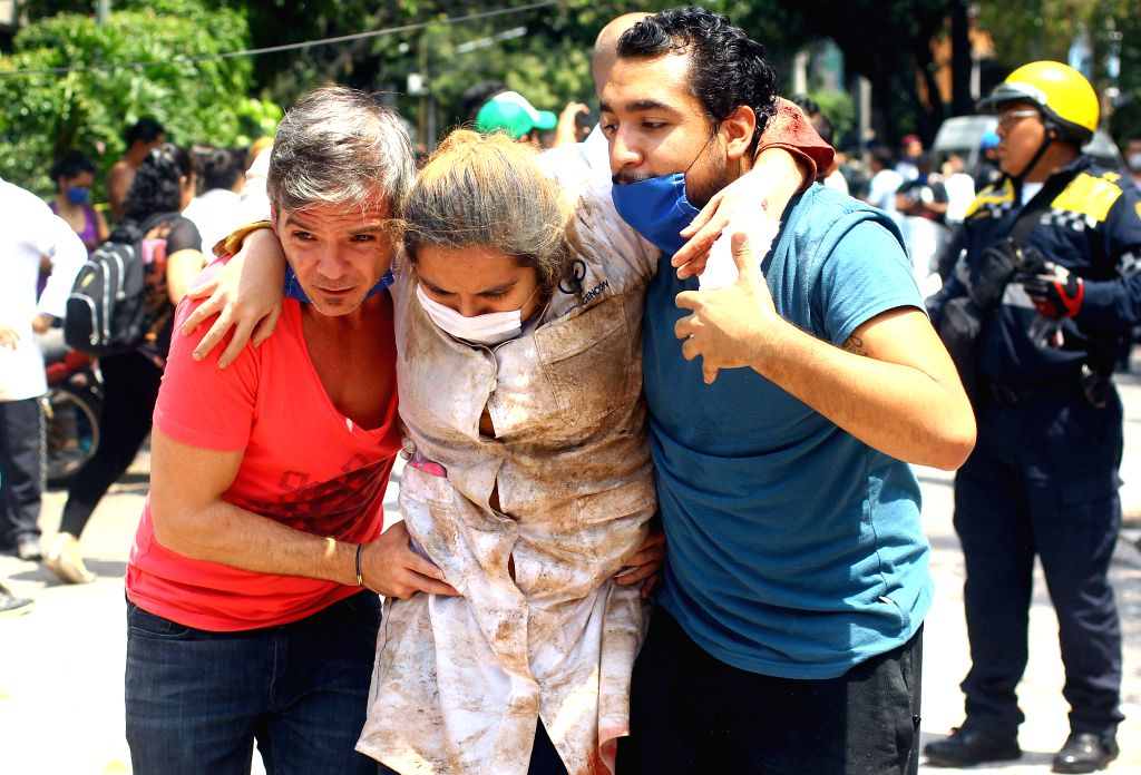 MEXICO CITY, Sept. 19, 2017 - People help a woman after an earthquake in Mexico City, capital of Mexico, on Sept. 19, 2017. At least 47 people were killed in a powerful 7.1-magnitude earthquake that ...