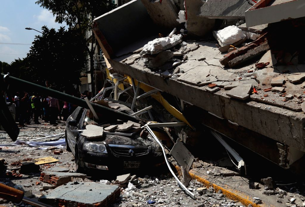 MEXICO CITY, Sept. 19, 2017 - Photo taken on Sept. 19, 2017 shows a vehicle crushed by debris from a collapsed building after an earthquake in Mexico City, capital of Mexico. At least 47 people were ...