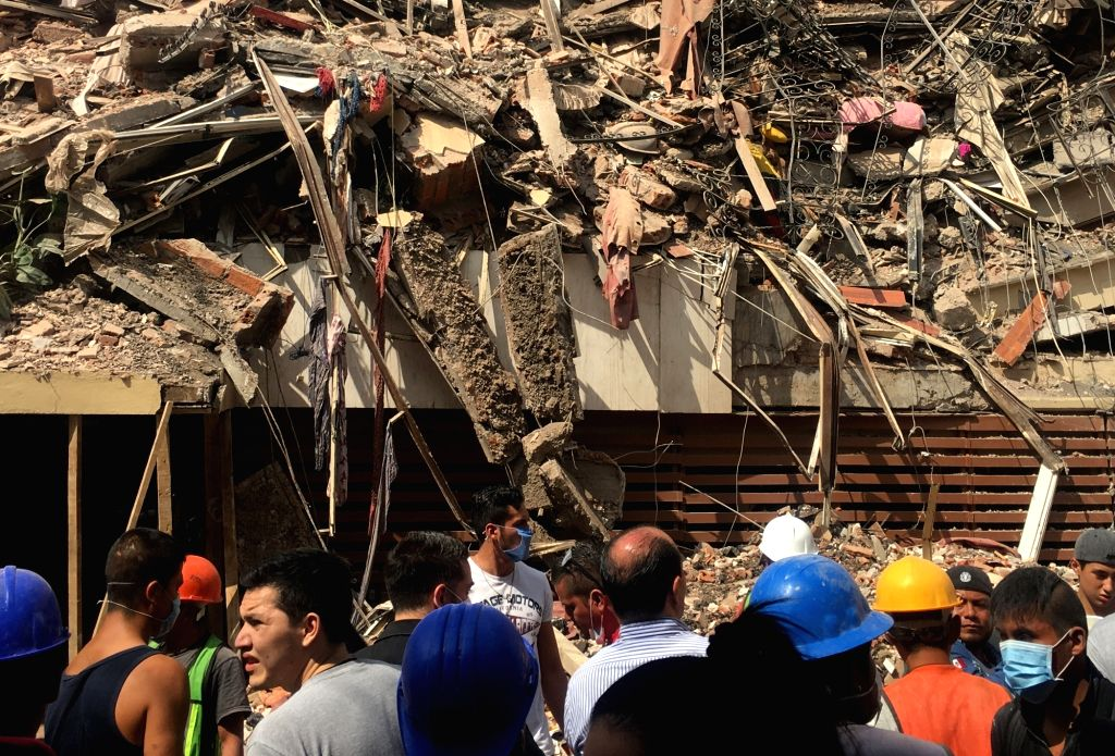 MEXICO CITY, Sept. 20, 2017 - Image taken with a mobile phone shows people watching a collapsed building after an earthquake in Mexico City, capital of Mexico, on Sept. 19, 2017. More than 100 people ...
