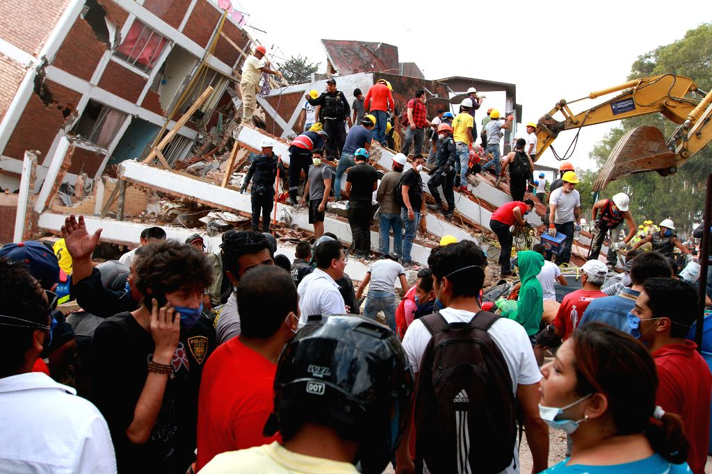 MEXICO CITY, Sept. 20, 2017 - People search for victims on a collapsed building after an earthquake in Mexico City, capital of Mexico, on Sept. 19, 2017. The death toll from a 7.1-magnitude ...