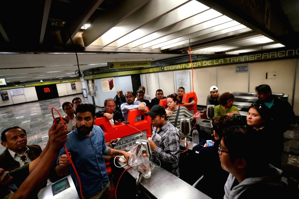 MEXICO CITY, Sept. 20, 2017 - People use cable extensions to charge their mobile phones at a subway station after an earthquake, in Mexico City, capital of Mexico, Sept. 20, 2017. At least 216 people ...