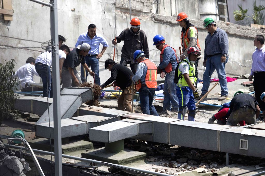 MEXICO CITY, Sept. 20, 2017 - People work on the roof of a collapsed building after an earthquake in Mexico City, capital of Mexico, on Sept. 19, 2017. More than 100 people were killed in a powerful ...