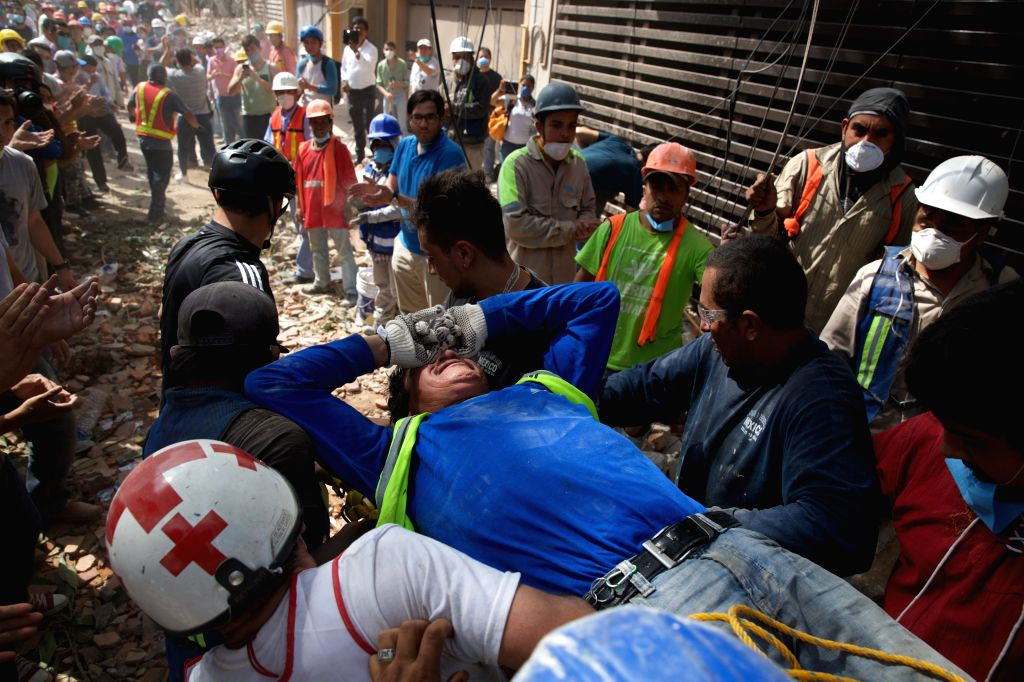 MEXICO CITY, Sept. 20, 2017 - Rescuers and volunteers move an injured man after an earthquake in Mexico City, capital of Mexico, on Sept. 19, 2017. At least 216 people have been killed after a ...