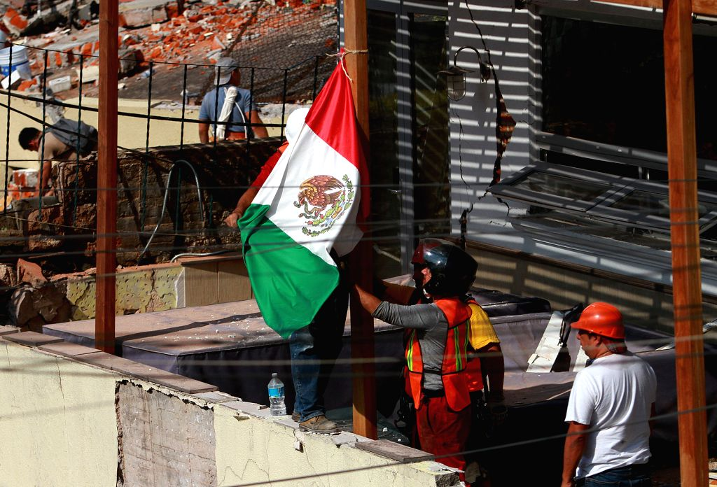 MEXICO CITY, Sept. 20, 2017 - Rescuers hoist a Mexican national flag at a damaged building after an earthquake in Mexico City, capital of Mexico, on Sept. 19, 2017. At least 216 people have been ...