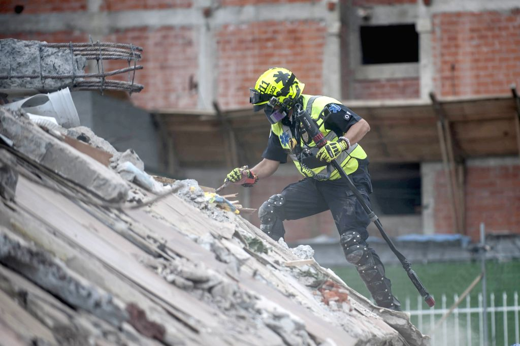 MEXICO CITY, Sept. 21, 2017 - A rescuer searches for survivors after an earthquake in Mexico City, capital of Mexico, on Sept. 20, 2017. Elements from the civil protection corps, Red Cross, army, ...