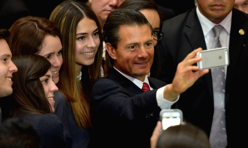 "Image provided by Mexico's Presidency shows Mexican President Enrique Pena Nieto taking a picture during the presentation of the program ""Reforms in ..."