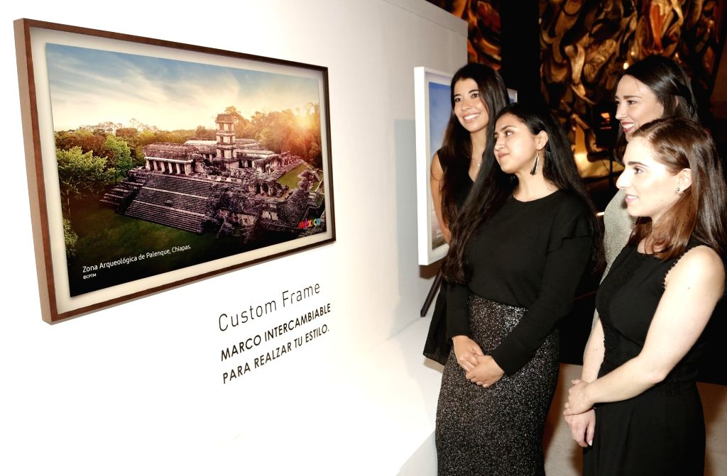 Mexico City: Spectators watch Samsung Electronics Co.'s The Frame television at a gallery in Mexico City on June 28, 2017, with a bezel resembling a picture frame, The Frame easily transforms into a ...