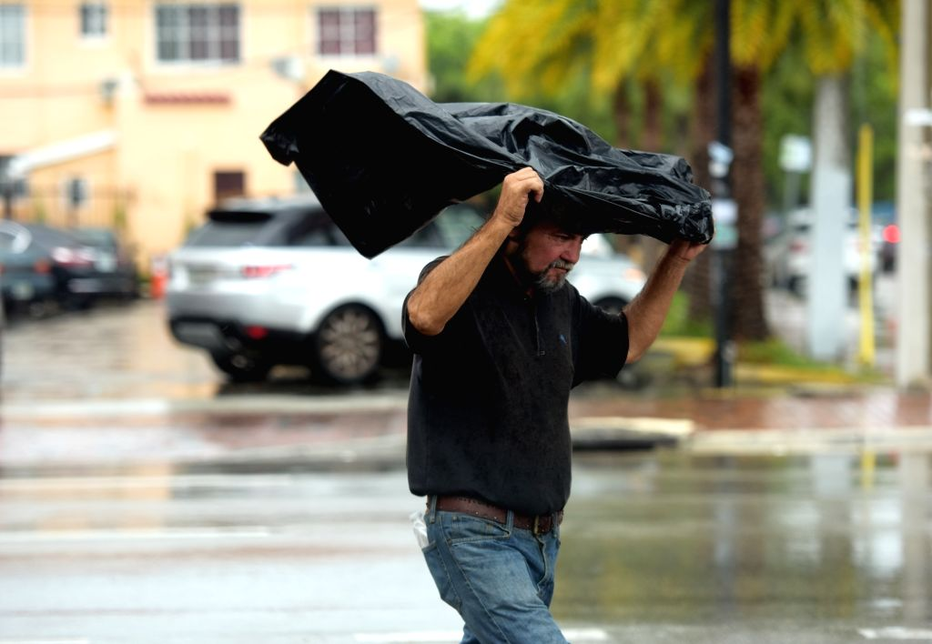 "MIAMI, Sept. 10, 2017 - A man walks in rain as hurricane ""Irma"" is approaching, in Miami, Florida, the United States, Sept. 9, 2017. About 5.6 million people in Florida have been ordered to ..."