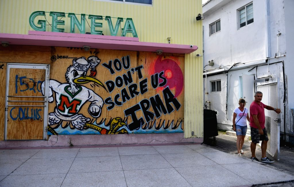 """MIAMI, Sept. 9, 2017 - Peopl walk past a message reading """"You Don't Scare Us, Irma"""" on a plywood used to protect the windows of a building as hurricane Irma approaches in Miami of Florida, ..."""