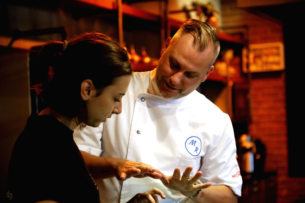 Michelin-starred German chef Michael Riemenschneider (R) instructs a young chef at his restaurant in Istanbul, Turkey, Aug. 12, 2020. After spending almost four ...