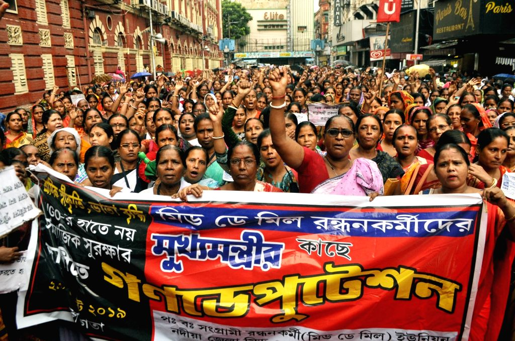 Mid-day meal workers participate in a protest rally to press for their various demands during rains, in Kolkata on Aug 29, 2019.