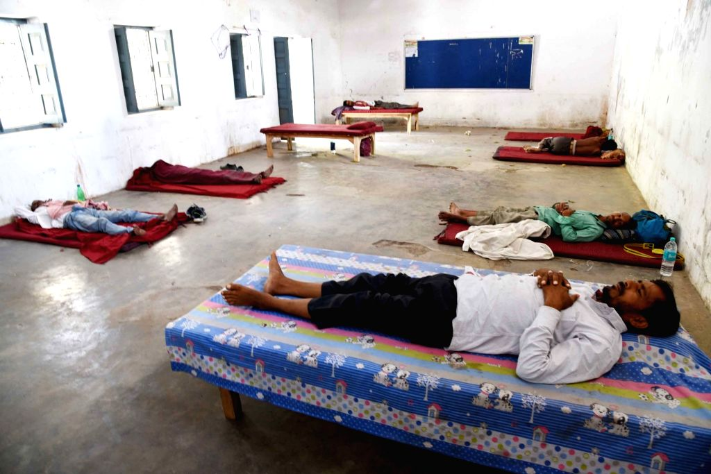 Migrant laborers take a nap at a relief camp set up at the College of Commerce, Arts & Science during a 21-day nationwide lockdown imposed to contain the spread of novel coronavirus, in ...