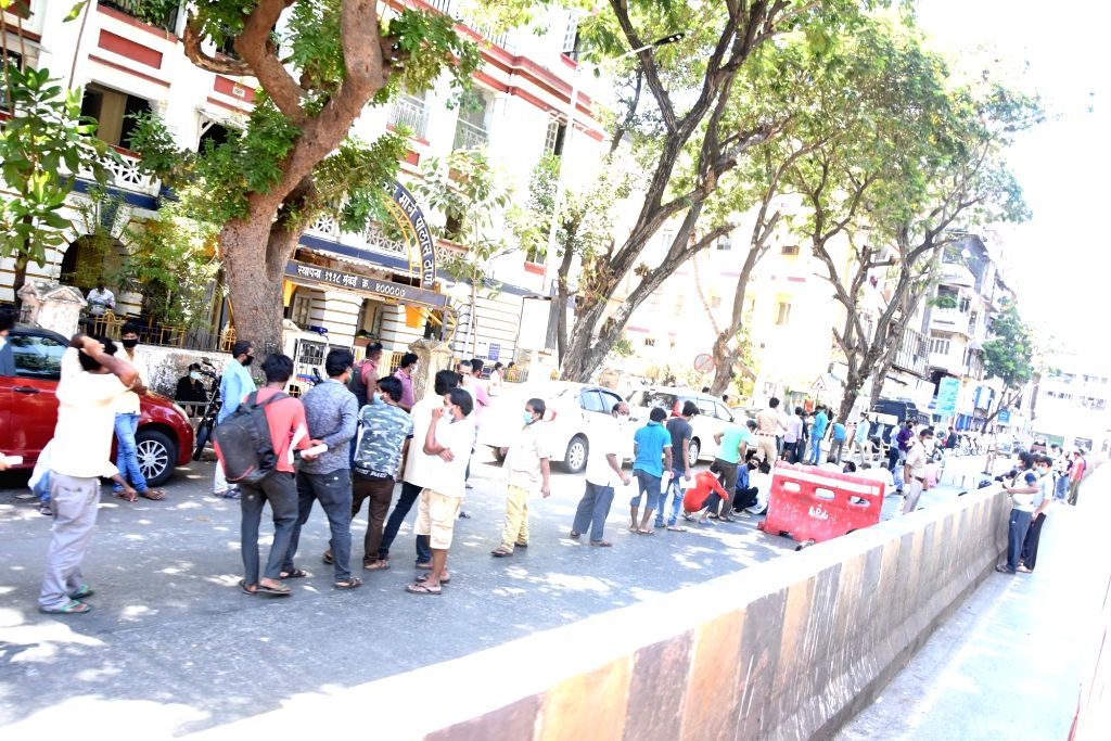 Migrant labourers stuck in Mumbai due to the ongoing nationwide lockdown imposed to mitigate the spread of COVID-19 queue up outside the Dadasaheb Bhadkamkar Marg Police Station to collect ...
