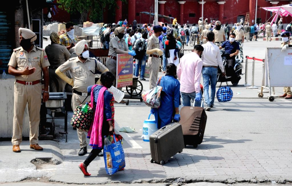 Migrant workers along with their families from Baraun in Uttar Pradesh arrive at the railway station to go back to their hometowns with a special train after the government eased a ...