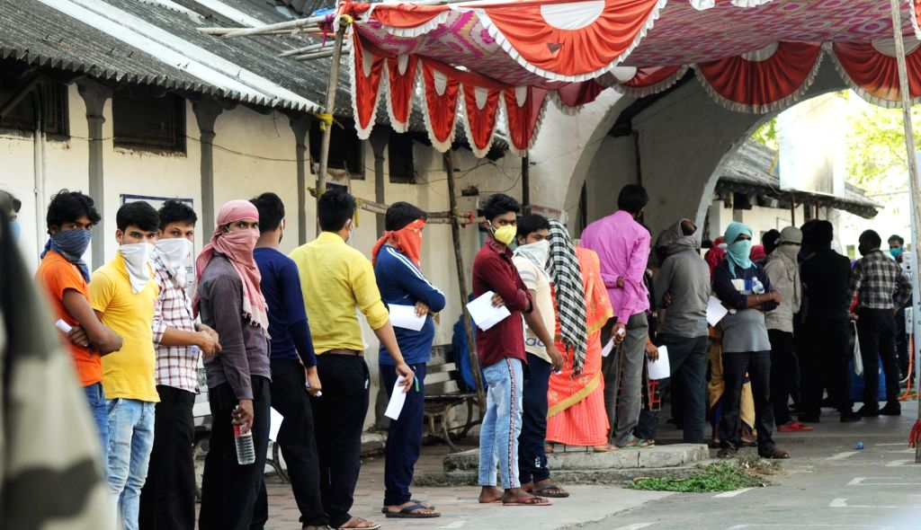 Migrant workers from different parts of the country who are stuck in Maharashtra due to the ongoing nationwide lockdown imposed to mitigate the spread of COVID-19, queue up to collect health ...