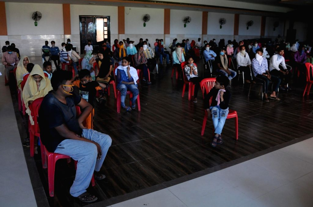 Migrant workers from Uttar Pradesh who were stranded in Punjab due to the ongoing nationwide lockdown imposed to mitigate the spread of coronavirus, maintain social distance as they wait to ...
