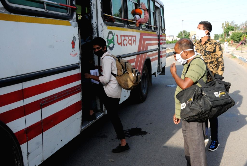 Migrant workers from Uttar Pradesh who were stranded in Punjab due to the ongoing nationwide lockdown imposed to mitigate the spread of coronavirus, on their way to the railway station from ...