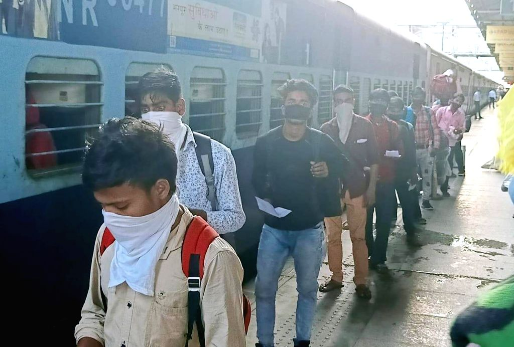 Migrant workers from Uttar Pradesh who were stranded in Punjab due to the ongoing nationwide lockdown imposed to mitigate the spread of coronavirus, arrive at Amritsar Junction railway ...