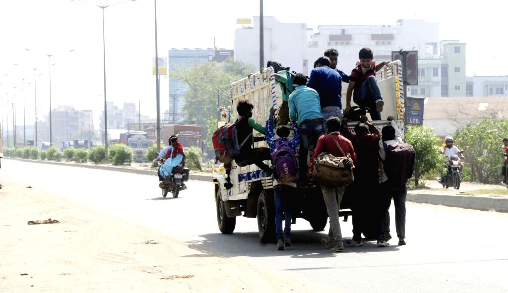 Migrant workers heading back home board a mini-truck on Day 5 of the 21-day countrywide lockdown imposed to contain the spread of novel coronavirus, in Patna on March 29, 2020.