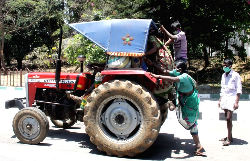 Migrant workers heading back home, board a tractor on Day 5 of the 21-day countrywide lockdown imposed to contain the spread of novel coronavirus, in Bengaluru on March 29, 2020.