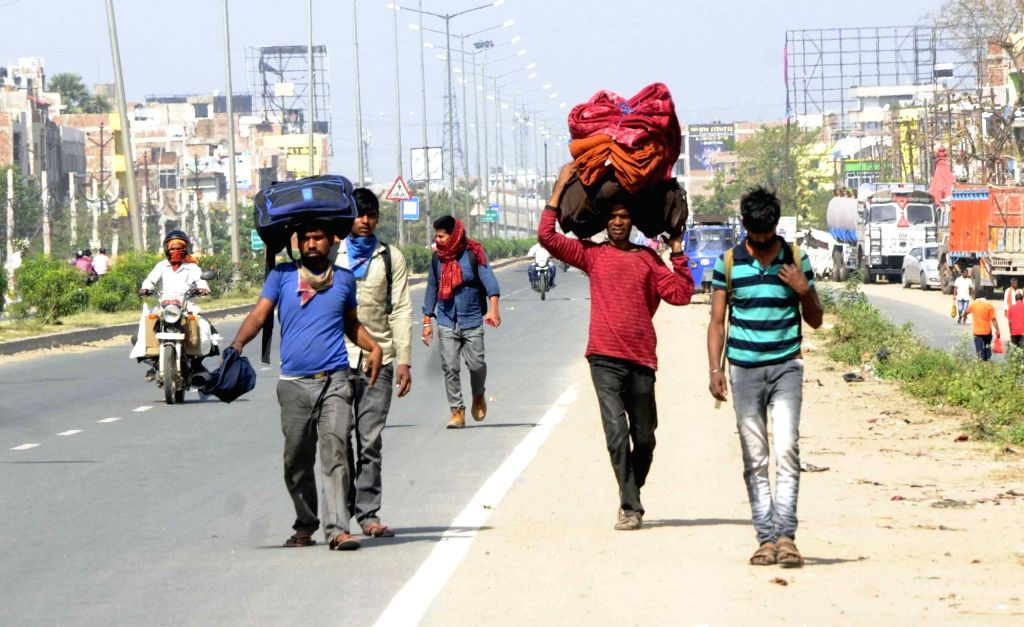 Migrant workers heading back home search for transport on Day 5 of the 21-day countrywide lockdown imposed to contain the spread of novel coronavirus, in Patna on March 29, 2020.