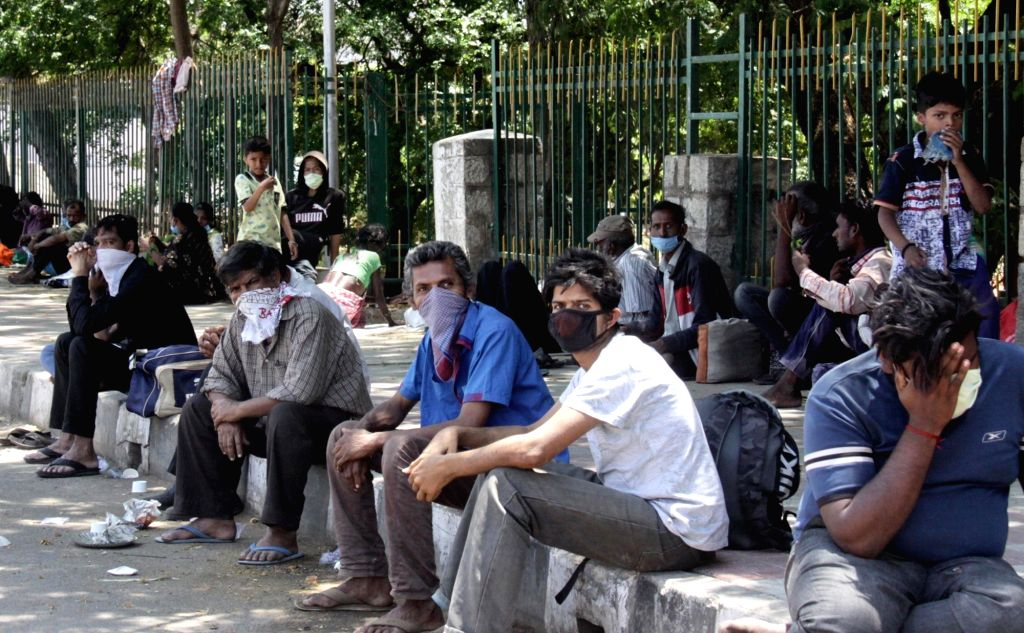 Migrant workers trying to return home wait for transport near Majestic Bus Stand on Day 6 of the 21-day countrywide lockdown imposed to contain the spread of novel coronavirus, in ...