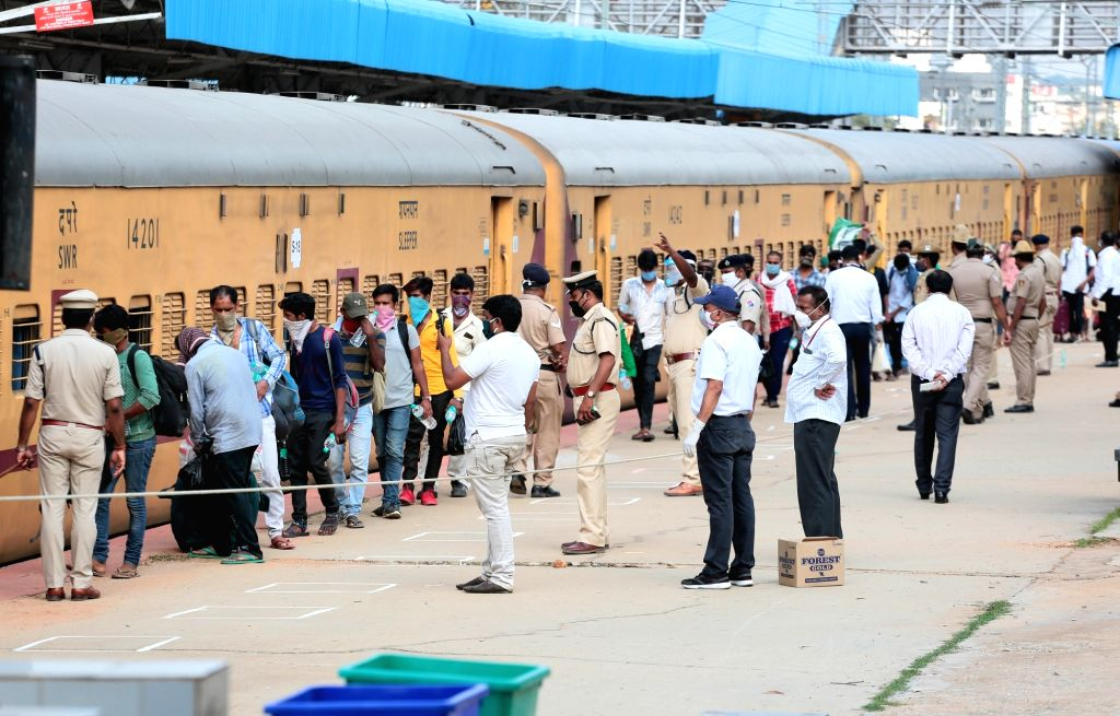 Migrant workers wait in a queue to board a Shramik Special train to reach their native place in Uttar Pradesh at Chikkanbanavara railway, in Bengaluru on May 8, 2020.