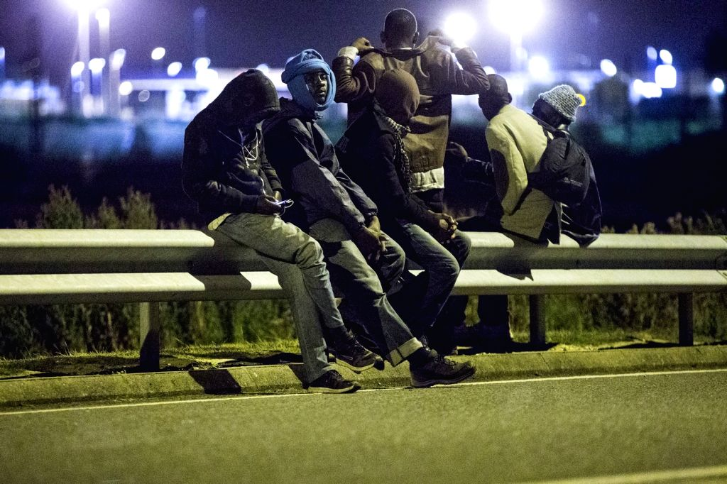 Migrants linger on the Shuttle railroad looking for a chance to jump over the fence and access the Channel Tunnel, in Calais, northern France, Aug. 6, 2015. Calais, ...