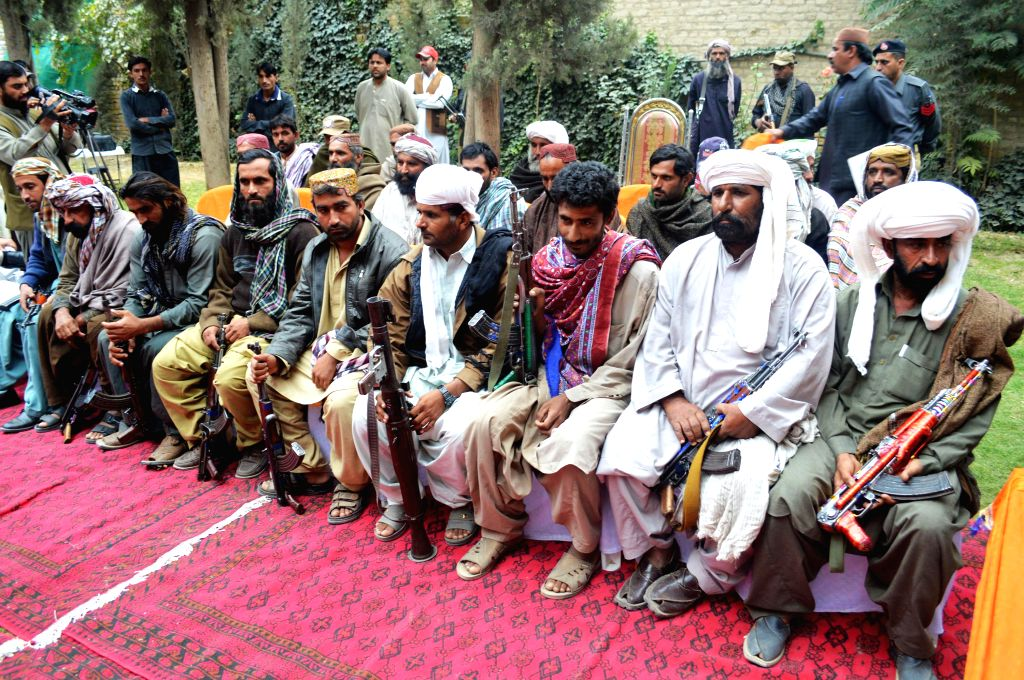 Militants sit before handing over their weapons during a surrender ceremony in Quetta, Pakistan, Oct. 29, 2015. A total of 23 militants belonging to Marri tribe have ...