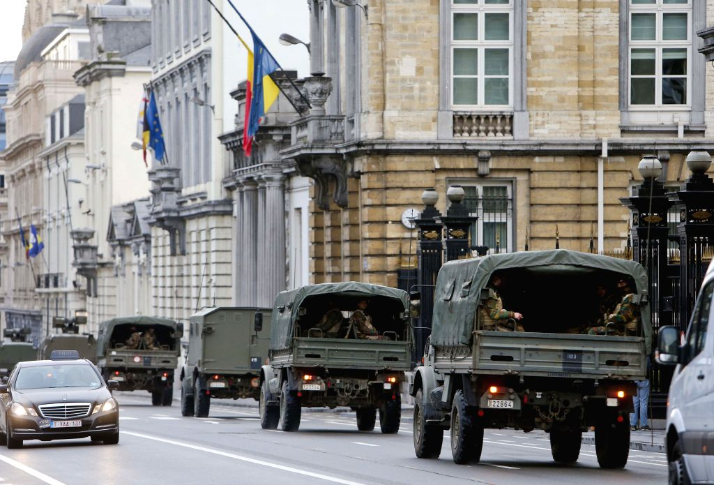 Military vehicles are seen running through Brussels, capital of Belgium, on Nov. 21, 2015. The terror threat level in the Brussels region was increased to ... - Charles Michel
