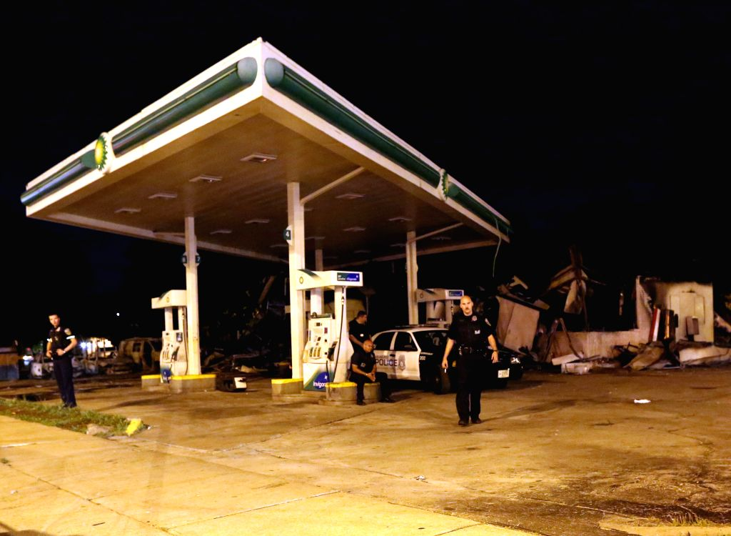 MILWAUKEE, Aug. 15, 2016 - Policemen stand guard at a gas station damaged by violence in Milwaukee, U.S. state of Wisconsin, Aug. 14, 2016. Gunshots were fired, businesses were set ablaze, people ...