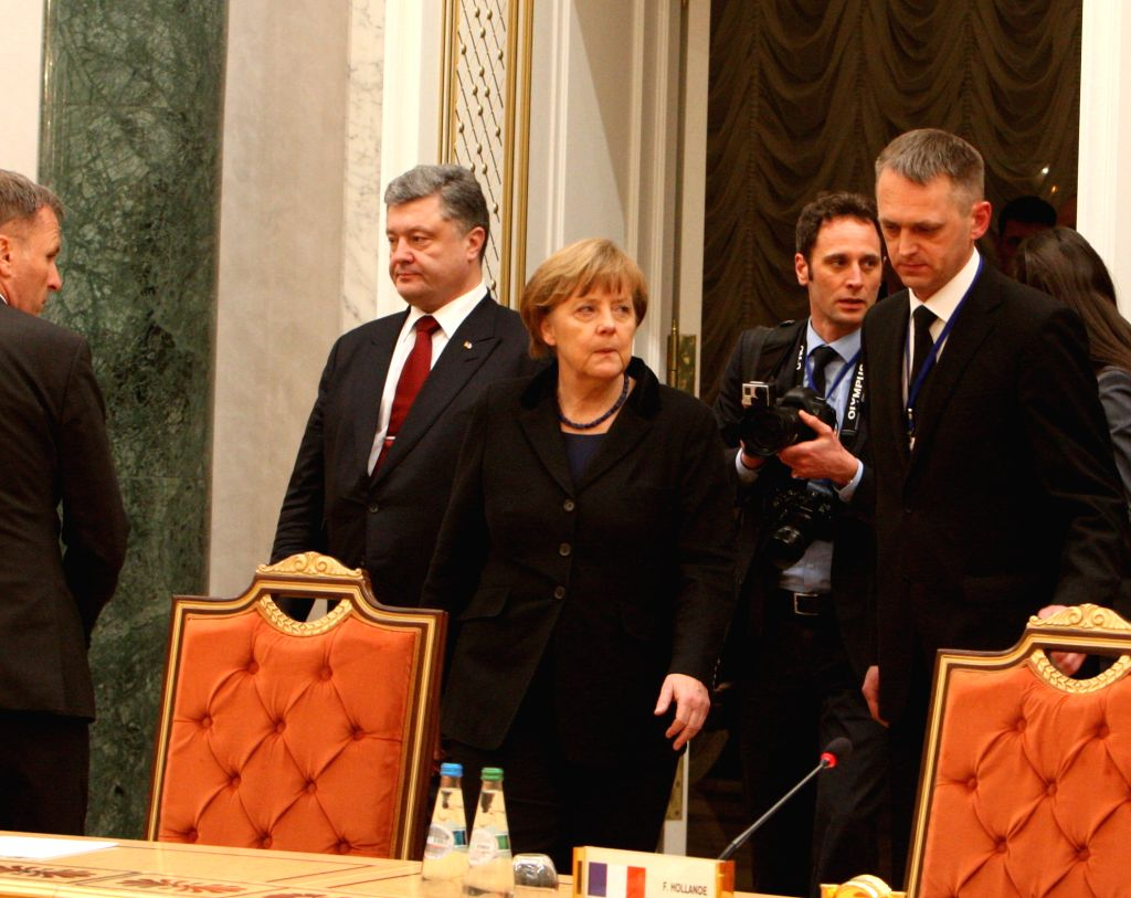 Ukrainian President Petro Poroshenko (1st L) and German Chancellor (C) arrive for the four-way peace talks on the Ukraine crisis in Minsk, Belarus, on Feb. 11, 2015. .