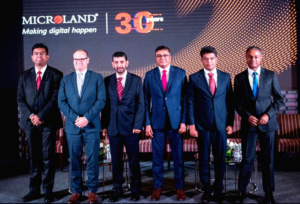 Mircoland Ltd. Founder, Chairman and MD Pradeep Kar posing with his team for a group photograph during a press conference regarding company's 30th year anniversary celebration, in ...
